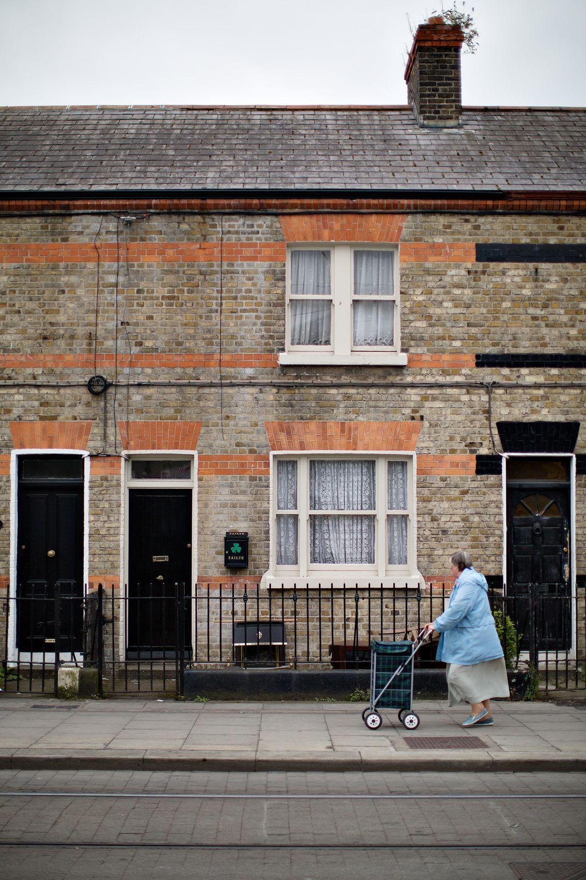 Eine Frau schiebt einen Trolley durch Dublin. An einem der Häuser ziert ein großes Kleeblatt – ...