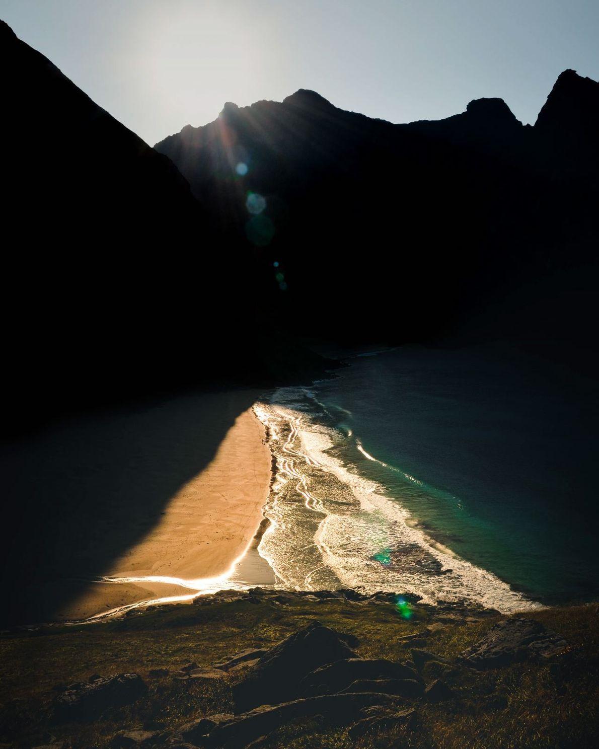 Auf den Lofoten erhellt die Sonne einen Teil des Strandes, der größtenteils im kühlen Schatten der ...