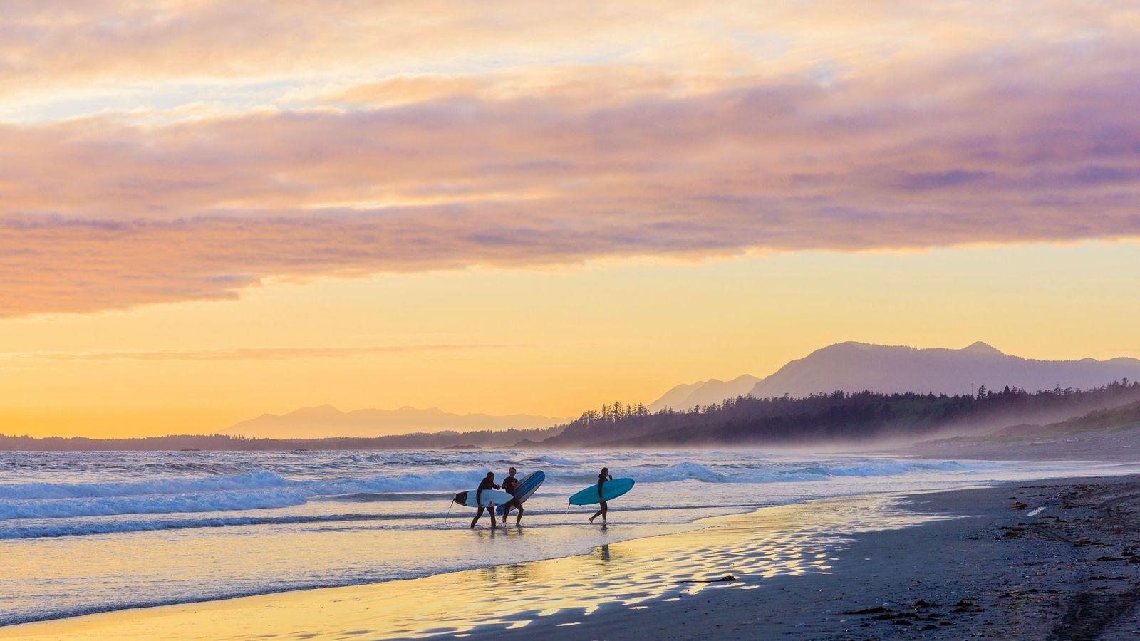 Surfer laufen bei Sonnenuntergang über den Long Beach des Pacific-Rim-Nationalparks auf Vancouver Island in British Columbia.