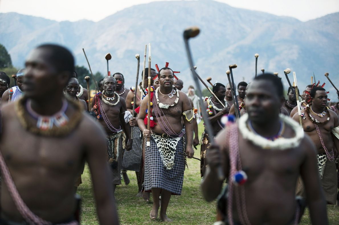 ESWATINI König Mswati III. (Mitte) tanzt bei einer traditionellen Schilftanzzeremonie mit seinen Männern vor Jungfrauen in Ludzidzini …