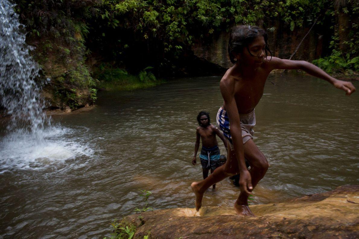 Jungs schwimmen in einem Fluss. Die Badestelle liegt weit genug landeinwärts, um vor Leistenkrokodilen geschützt zu ...