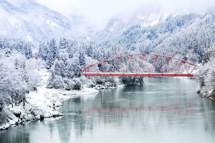 Eine rote Brücke leuchtet in der verschneiten Winterlandschaft Japans.