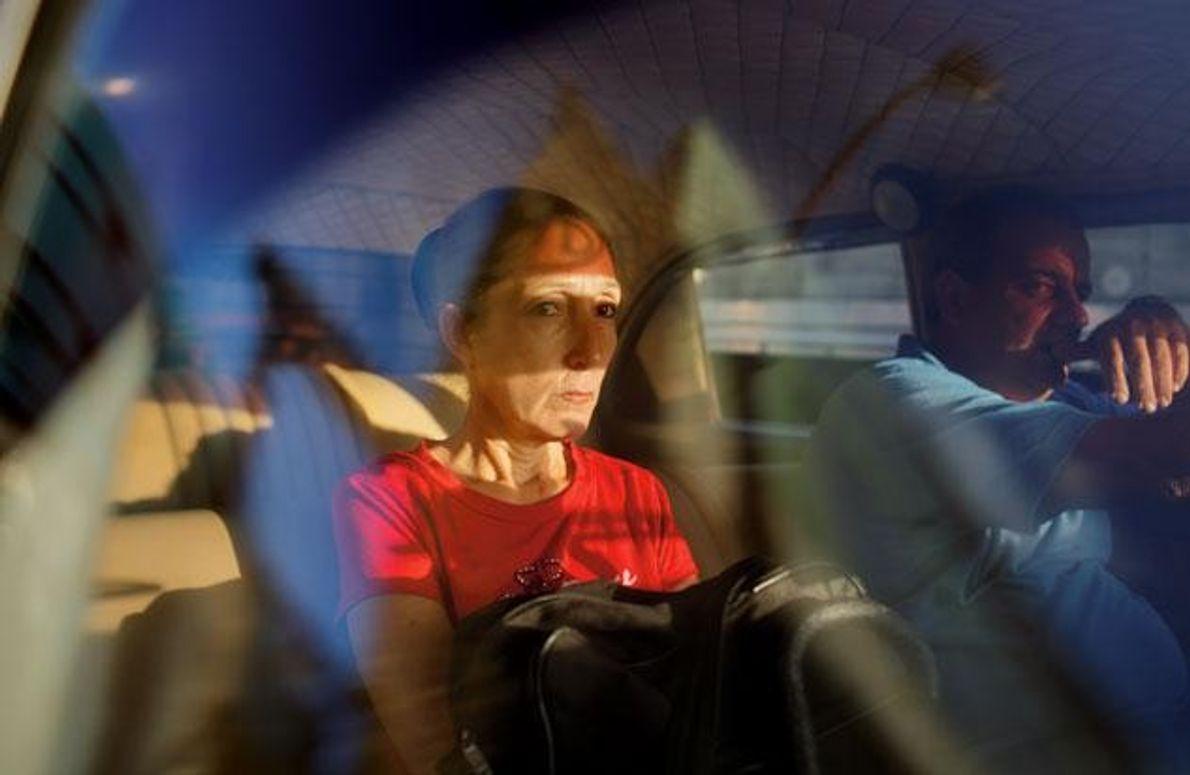 Eine Frau in Havanna, unterwegs in einem Taxi. Das Auto ist eine der uralten Karossen aus …