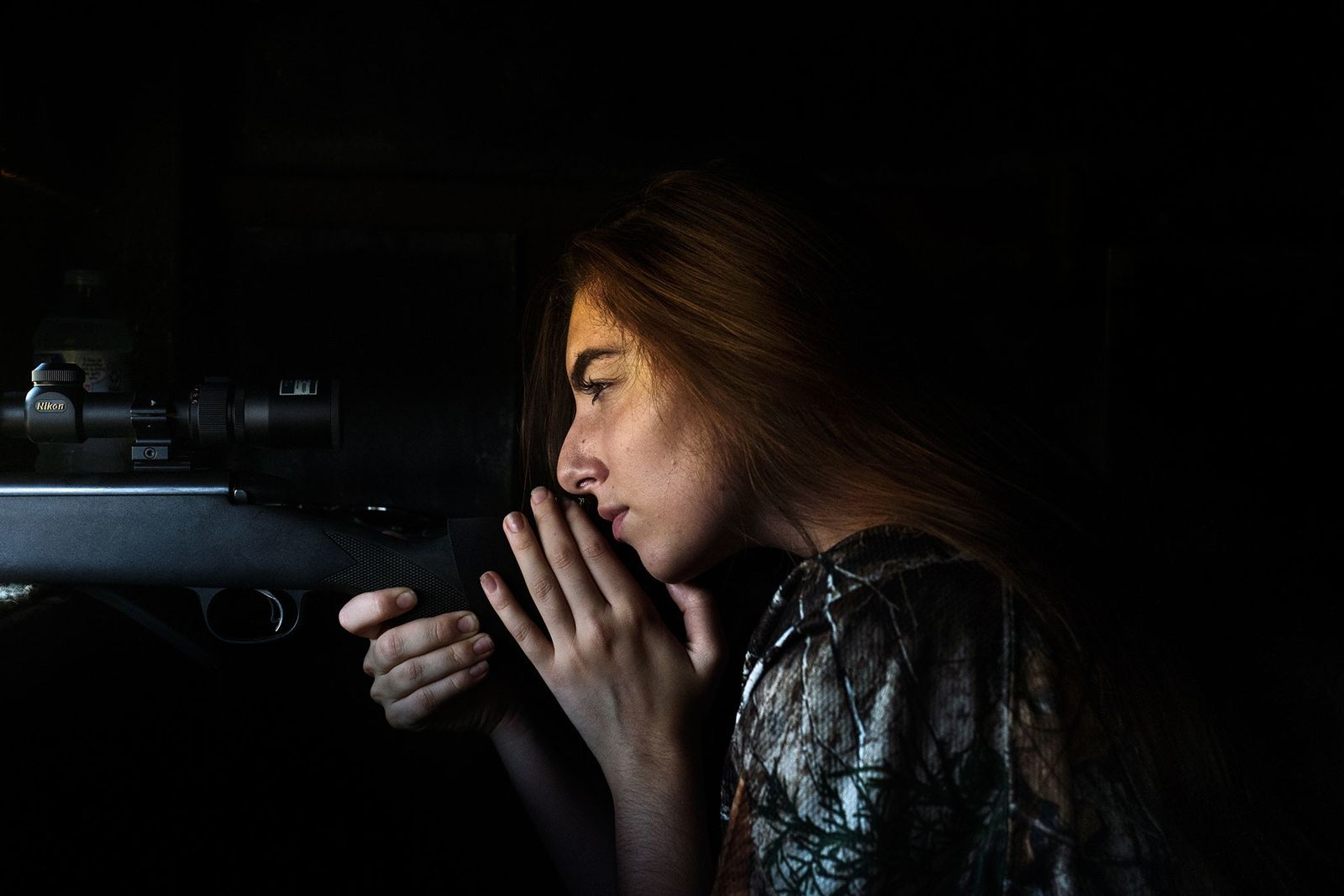 Grace Ingrande, 17, waits for a clear shot at an axis deer in a hunting blind ...