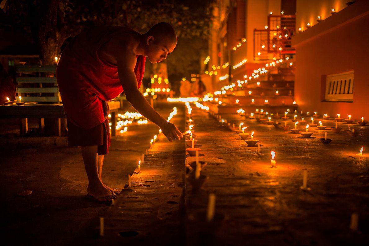 Mann zündet eine vieler Kerzen auf dem Thadingyut Festival an