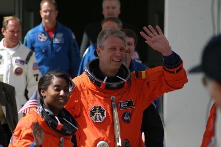 Astronaut Thomas Reiter und NASA-Kollegin Stephanie Wilson winken in orangenen Raumanzügen
