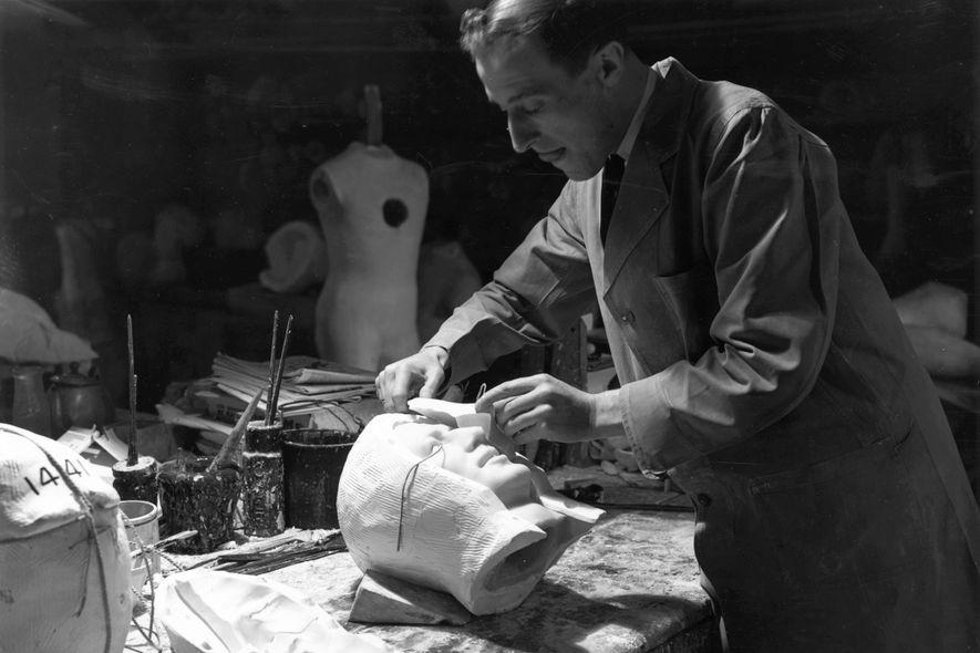 Ein Künstler entfernt bei Madame Tussauds in London die Gipsform von einem Kopf.