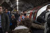 Ein Mitarbeiter der Londoner U-Bahn trägt bei der Arbeit einen Mundschutz, während Fahrgäste am 3. März ...