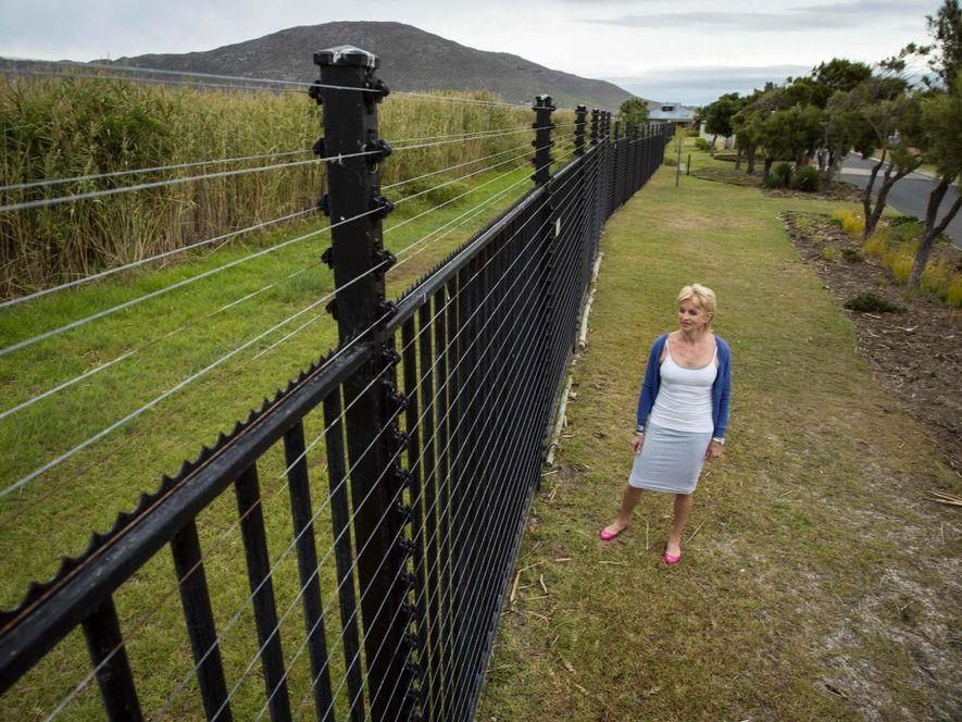 Jenseits der Feuchtgebiete, nur ein paar Hundert Meter von Masiphumelele entfernt, läuft Danie Kagan an dem elektrischen Zaun entlang, der die Gemeinde Lakes Michelle bei Kapstadt umschließt.