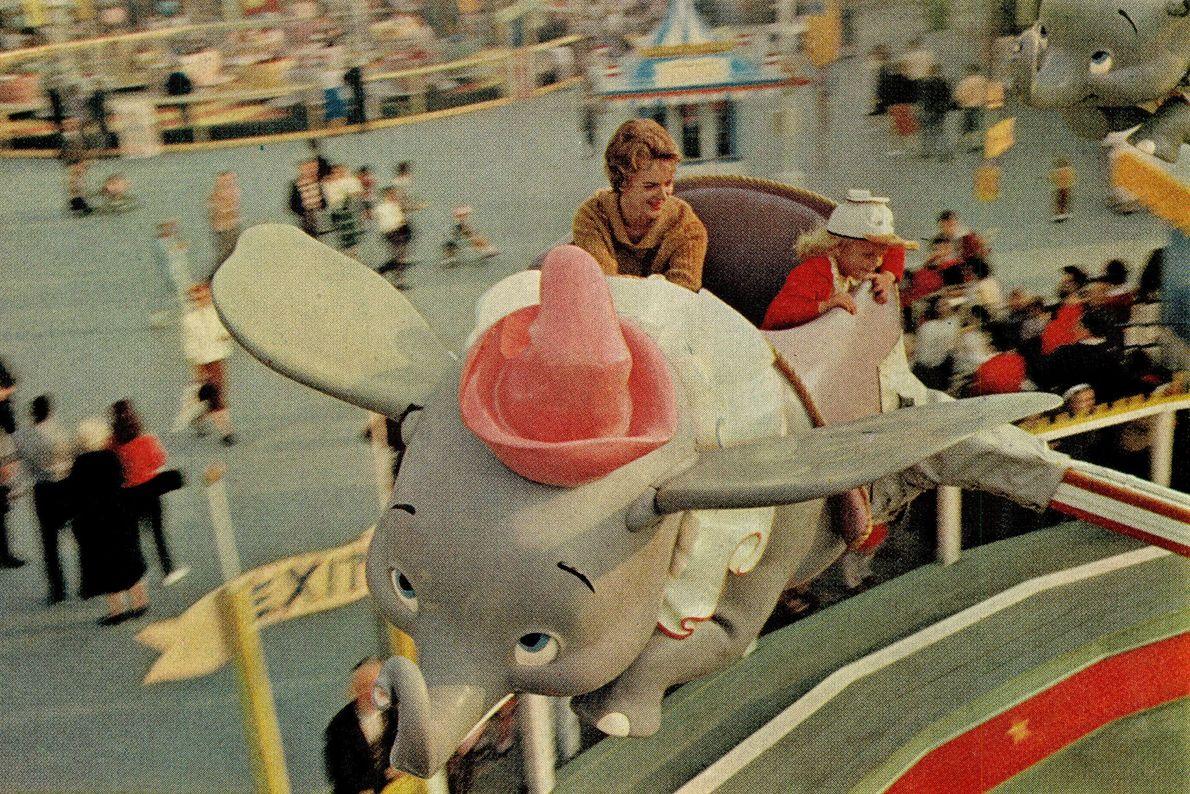 """Eine Familie fährt in dem Fahrgeschäft """"Dumbo, the Flying Elephant"""" mit, das auf dem Animationsfilm von ..."""