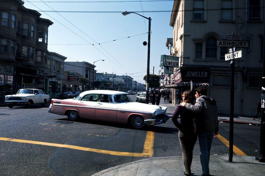 Ein junges Paar hält im Sommer der Liebe 1967 an einer Kreuzung der Straßen Haight und ...