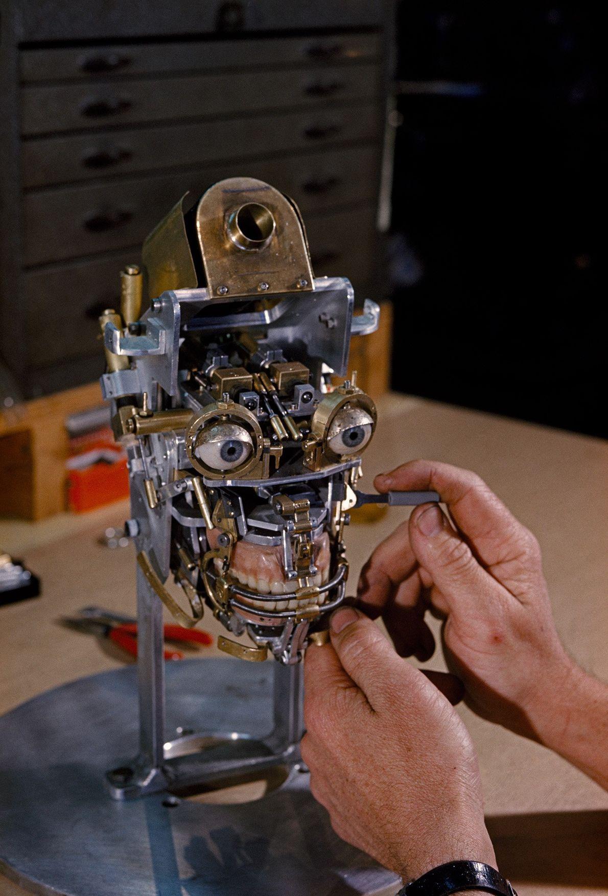 Ein Techniker arbeitet an einem mechanischen Kopf für einen Roboter.