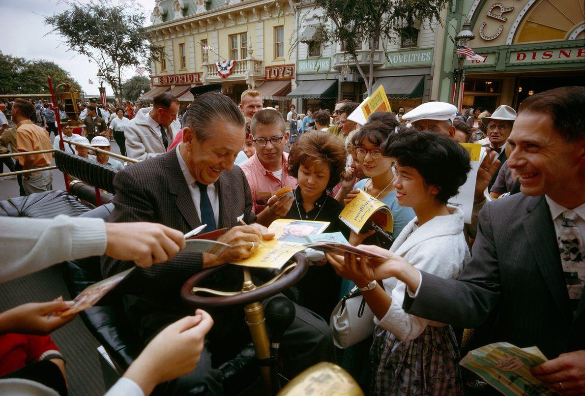 Walt Disney gibt auf der Main Street U.S.A. in Disneyland Autogramme.