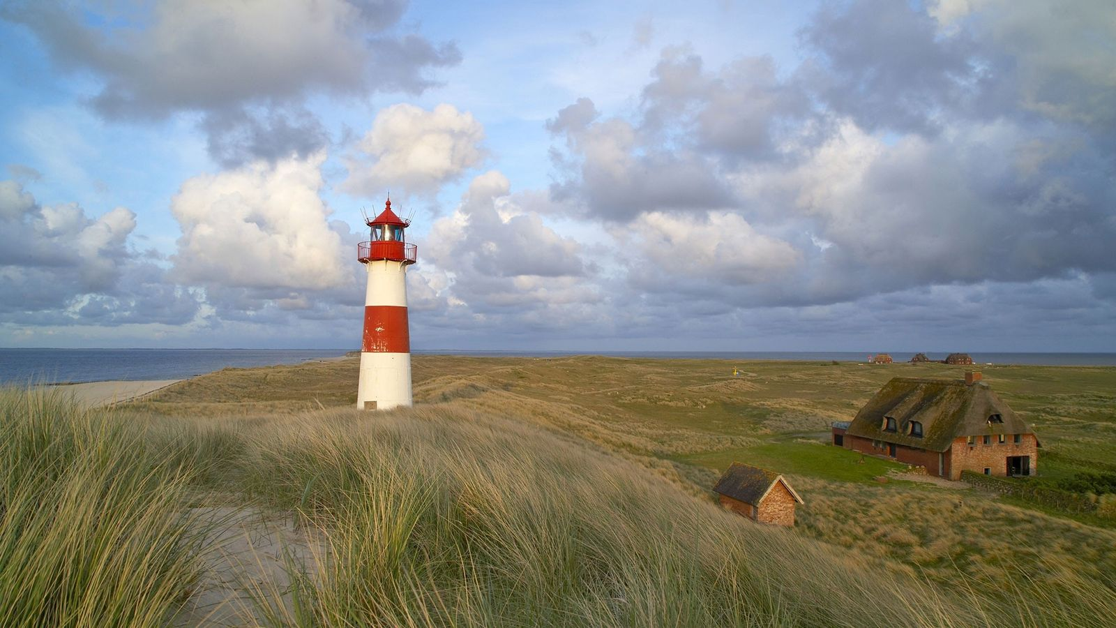 Ein Leuchtturm ragt über der Dünenlandschaft auf der deutschen Insel Sylt auf.
