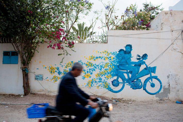 Wandmalerei einer Familie auf einem Mofa mit Blumen