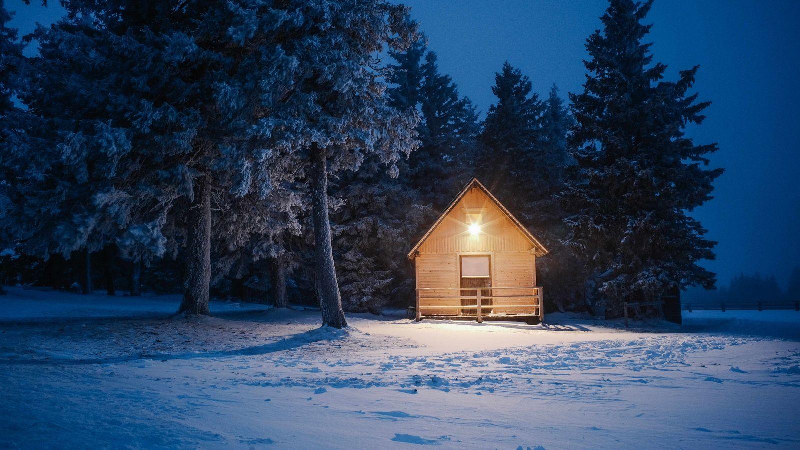 In der Abenddämmerung erhellt ein einladendes Licht eine der rustikalen Berghütten Roglas.