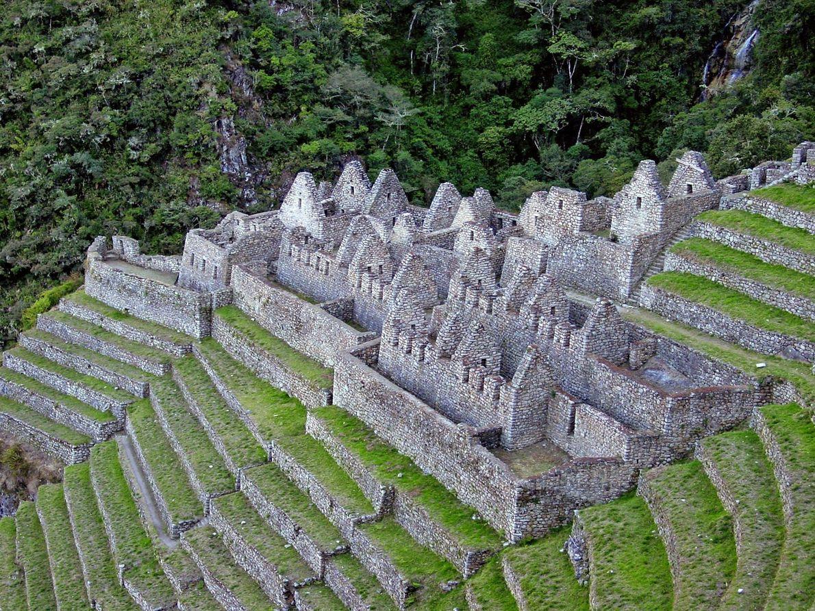 Auf einem grünen Hügel über dem Fluss Urubamba in Peru befinden sich die Terrassen und Ruinen ...