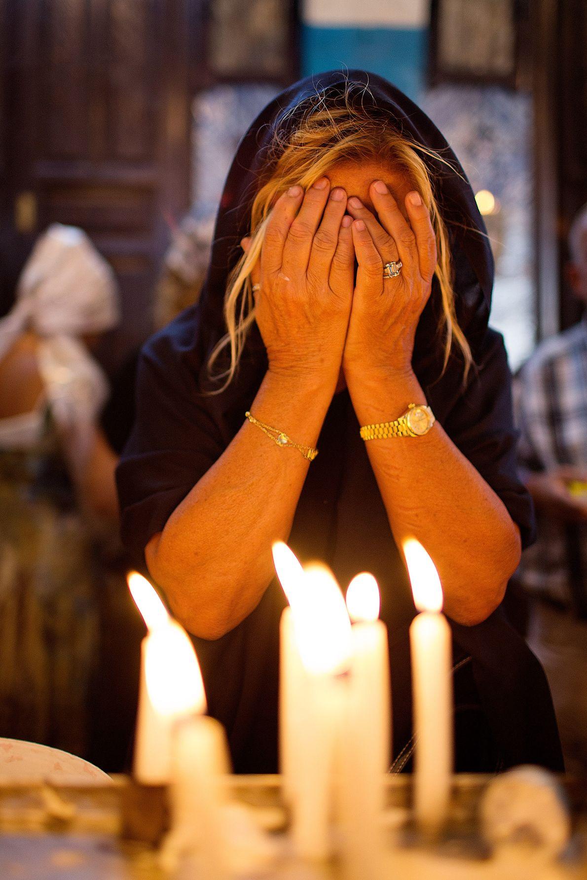 Trauernde Frau vor Kerzen