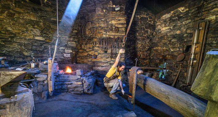Ein Schmied, oder ferreiro, zeigt die traditionellen Werkzeuge und Methoden, die auch heute noch verwendet werden, ...