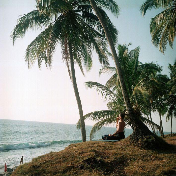 Ein Yogi meditiert am Schwarzen Strand von Kerala in Indien.