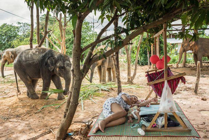 Siriyupha Chalermlam, 16, ruht sich mit ihrer Tochter Joy vor dem Haus ihres Vaters in ...