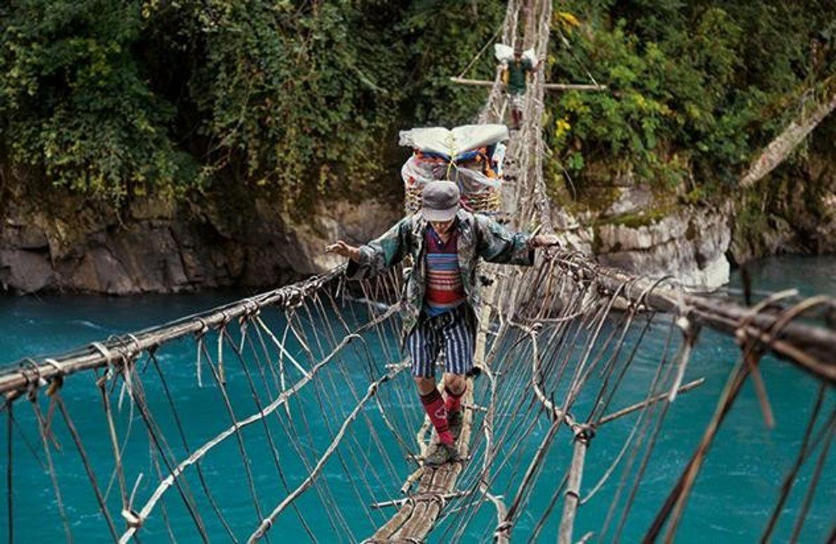 Mit einer 25 Kilo schweren Last auf dem Rücken balanciert dieser Träger über eine Hängebrücke. Weil …